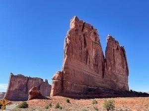 Tall spire-like orange rock structure jutting towas a deep blue sky
